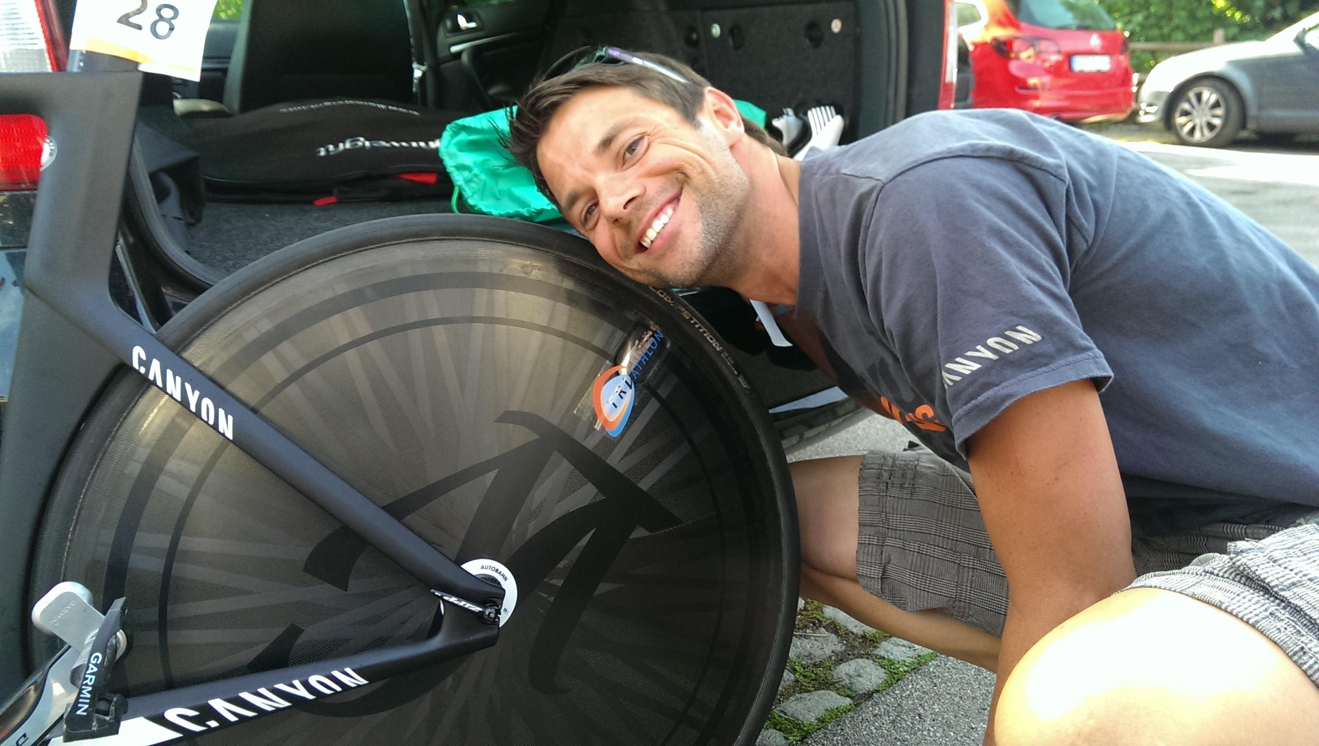 Triathlon-Profi Jens Kaiser klebt einen Chiemsee-Triathlon-Aufkleber auf sein Canyon Bike.